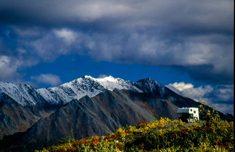 Travel Trailer By Snowcapped Mountains Against Cloudy Sky