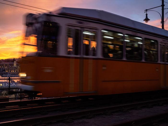 Train at railroad station against sky at dusk