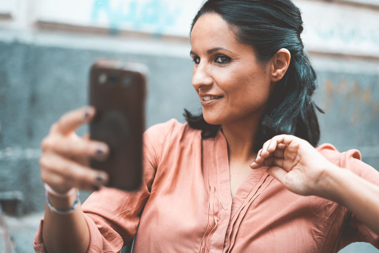 woman with mobile phone taking selfie Wireless Technology Mobile Phone Smart Phone Portable Information Device One Person Portrait Smiling Women Photography Themes Telephone Selfie Using Phone Adult Holding Beautiful Woman Adult Mid Adult Mirror Mirrorselfie