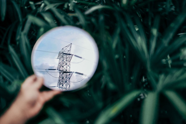 Close-up of hand holding mirror with reflection of electricity power lines