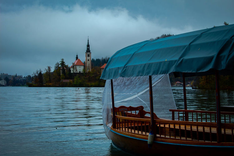 Boat in river by buildings against sky
