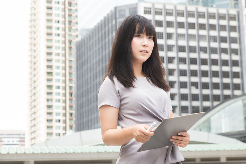 Young Businesswoman Standing Against Buildings In City