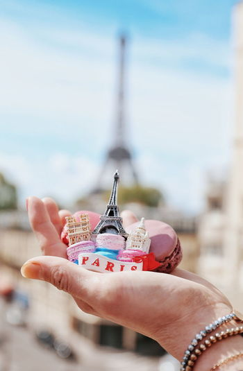 Cropped hand holding macaroons with figurines