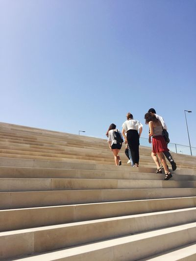 Low angle view of friends walking on staircase against clear blue sky