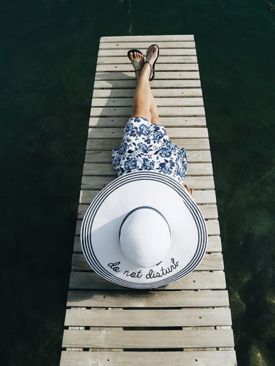 Woman in hat relaxing on pier over sea