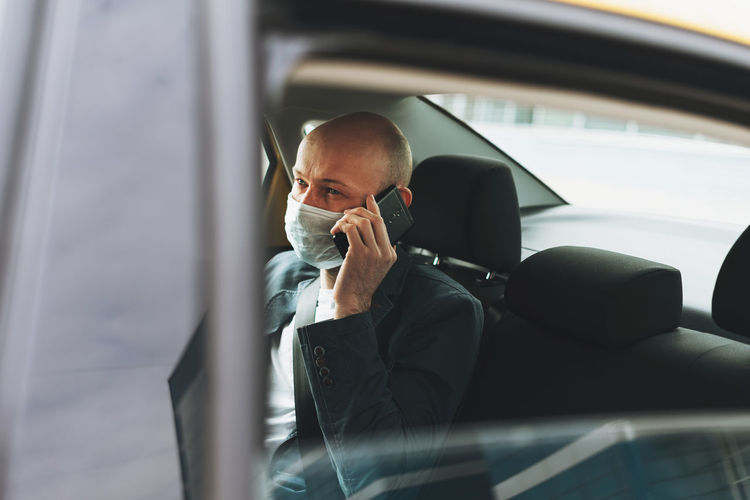 Businessman talking on phone while sitting in car