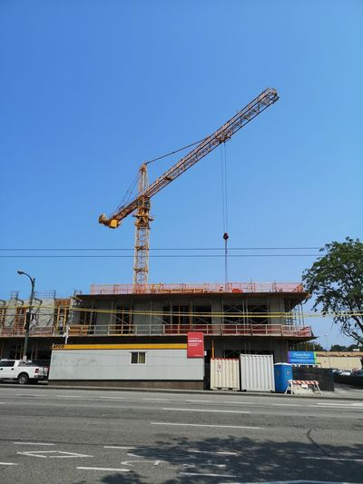 Crane at construction site against clear blue sky