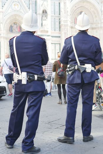 Rear View Of Police Force Standing On Street