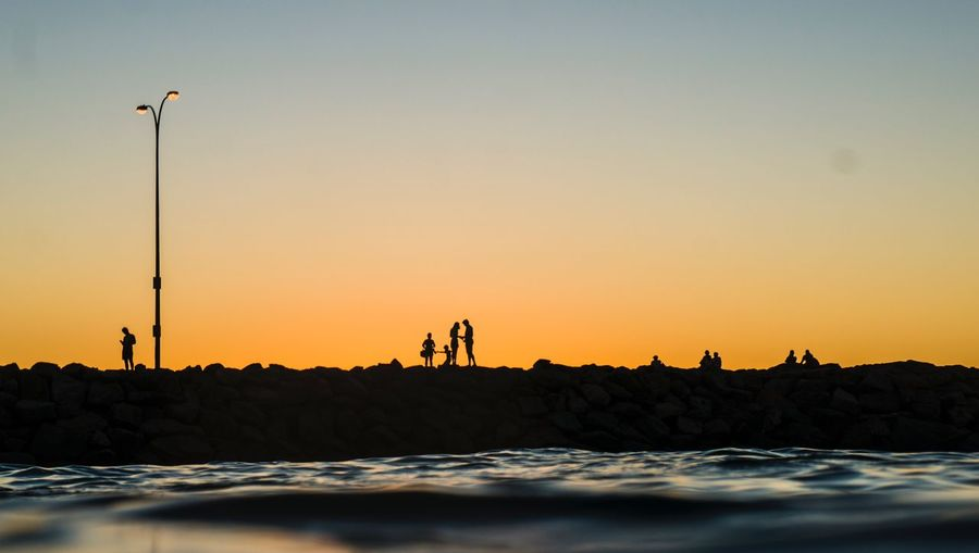 Silhouettes at sunset Blue Colour Vivid Sky Sunset Water Orange Color Leisure Activity Real People Waterfront Lifestyles Sea Beach Land Beauty In Nature Group Of People Silhouette Scenics - Nature Nature People Copy Space Outdoors Clear Sky