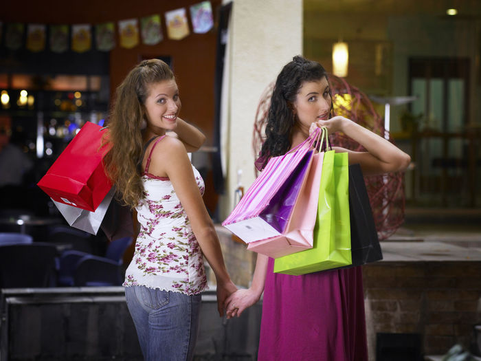Portrait Of Female Friends With Shopping Bags At Outdoor Cafe