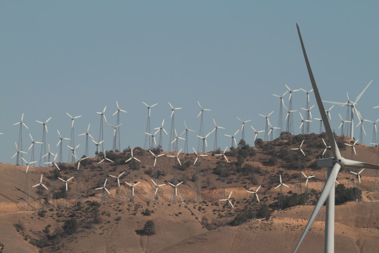 alternative energy, environment, renewable energy, nature, environmental conservation, sky, fuel and power generation, wind power, wind turbine, turbine, no people, clear sky, landscape, day, land, beauty in nature, fence, barrier, outdoors, non-urban scene, arid climate, climate