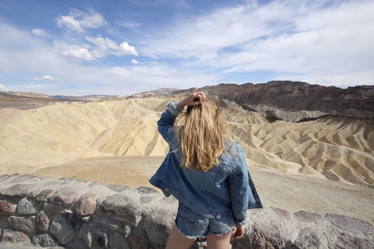 Young girl in casual clothing overlooking Zabriskie Point, the most famous viewpoint in the Death Valley National Park, USA Death Valley Jeans National Park Rear View Zabriskie Point Beauty In Nature Blond Hair Cloud - Sky Environment Girl Hair Iconic Landscape Leisure Activity Lifestyles Model Nature Non-urban Scene One Person Outdoors Overlooking Scenics - Nature Teenager Three Quarter Length Women