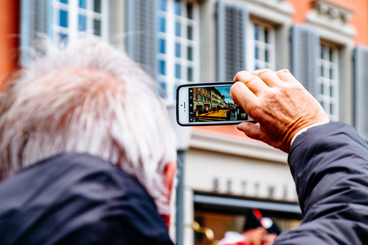 Cropped image of senior man photographing building