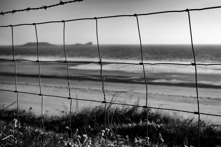Sea against sky seen through fence