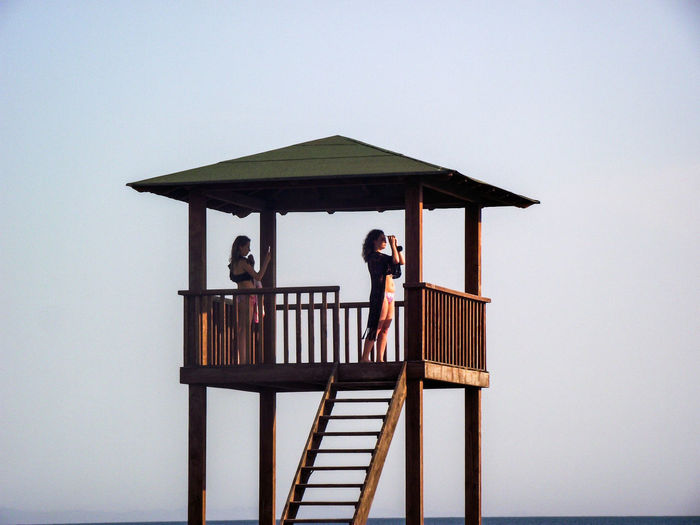 Women Standing In Lifeguard Hut Against Sky