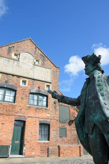 Statue of George Vancover Kings Lynn Norfolk with warehouse in background Sculpture Statue George Vancouver Kings Lynn Norfolk Norfolk Uk Docks Victorian Old Architecture Building Exterior