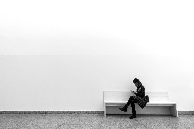 Full Length Of Woman Using Mobile Phone While Sitting On Bench Against Wall