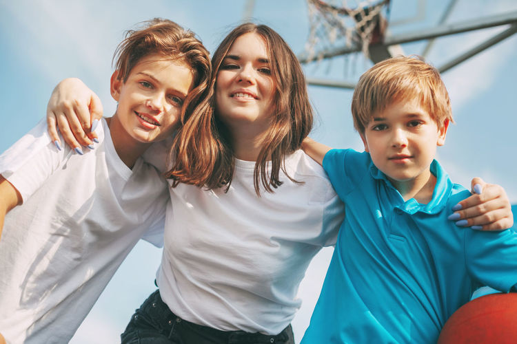 Low angle portrait of smiling siblings standing sky