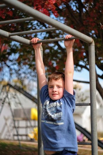 Portrait of boy hanging on railing in playground