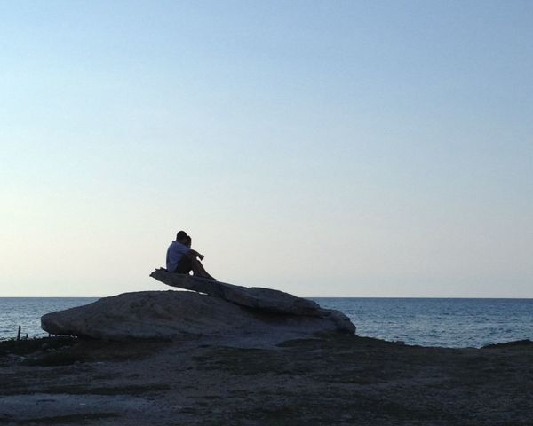 Embraced in sunset Calm Clear Sky Day Embrace Horizon Over Water Leisure Activity Lifestyles Negative Space Ocean Outdoors Relaxation Remote Rock Sea Sitting Sky Sunset Tranquil Scene Tranquility Vacations Water