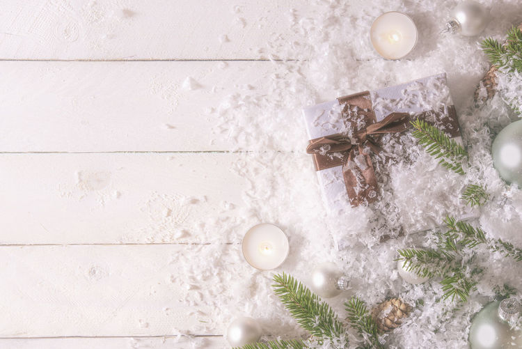Close-Up Of Christmas Gift Covered In Snow On Table