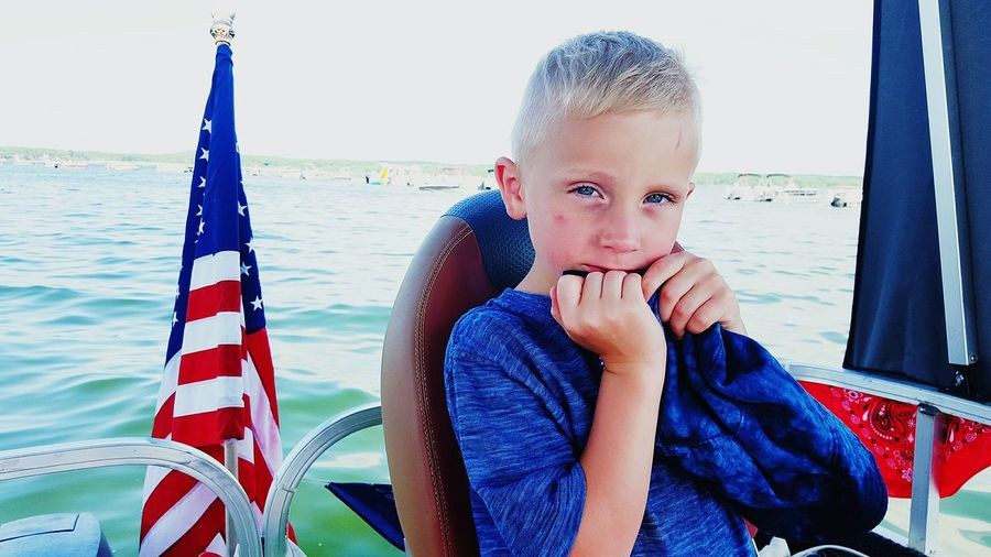 Portrait Of A Boy Sitting On A Boat With American Flag In Background