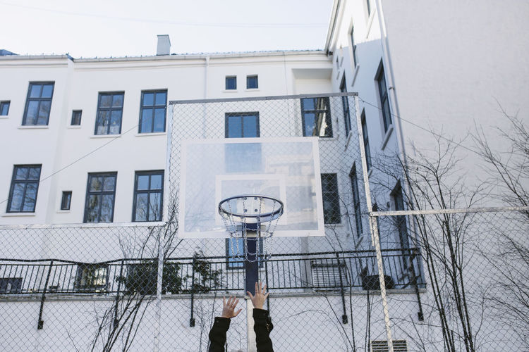 Low angle view of person playing basketball against building