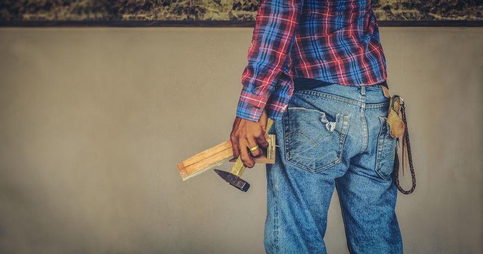 One Person Casual Clothing Holding Jeans Men Midsection Standing Work Tool Hand Tool Tool Adult Checked Pattern Real People Lifestyles Focus On Foreground Day Belt  Textile Plaid Shirt  Home Improvement Construction Pastel Craftsmanship  Occupation Skillful
