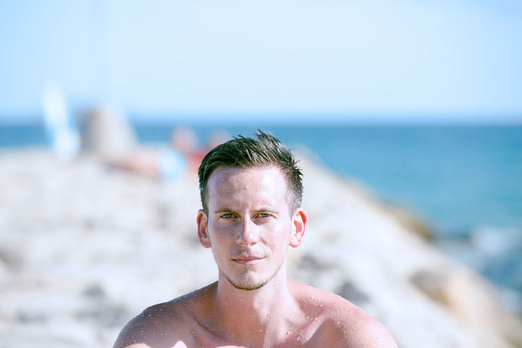 Close-up of shirtless man in sea against sky