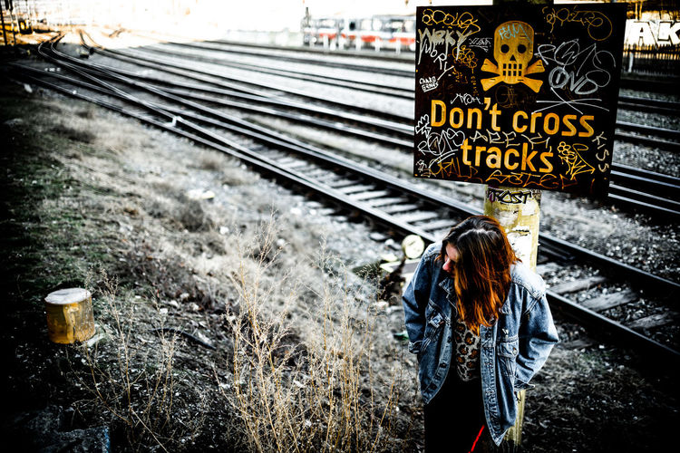 Rear view of woman standing by railroad tracks