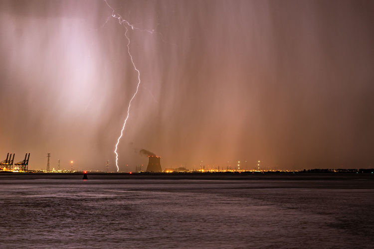 Lightning bolt strikes next to a nuclear power plant during a severe thunderstorm