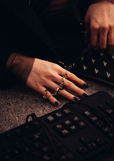 Cropped hands of woman using computer at table