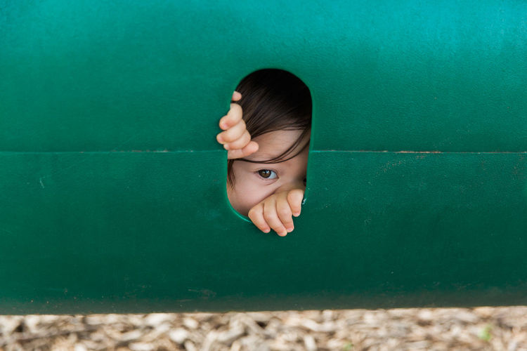 Playful Child Peeking Through Hole in Playground Children Funny Hands Lifestyle Adorable Child Childhood Close-up Cute Elementary Age Eye Fun Green Color Hole Leisure Activity Lifestyles One Person Outside Park Peeking Playground Playing Real People Summer Toddler