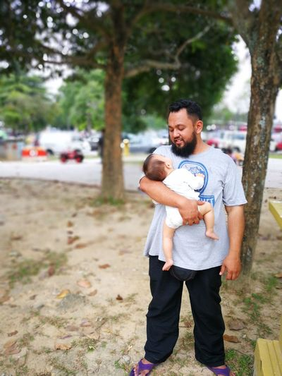 Smiling Father Carrying Baby While Standing In Park