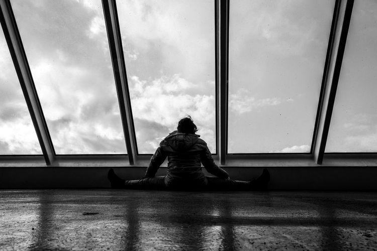 Rear view of man sitting on glass window