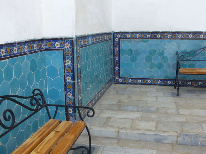 Wood benches in a Madrasah in Uzbekistan. Architecture Borders With Decoratons Built Structure Day Flowers Decoration Indoors  Muslim Art No People Octogonal Form Of The Tiles Pavement Religious Art Religious Architecture Wall With Blue Tiles White Wall With Tiles In The Lower Part Wood Benches Wood Benches With Beaten Iron