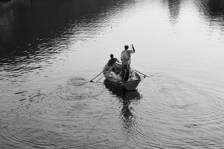 High angle view of men on boat in lake