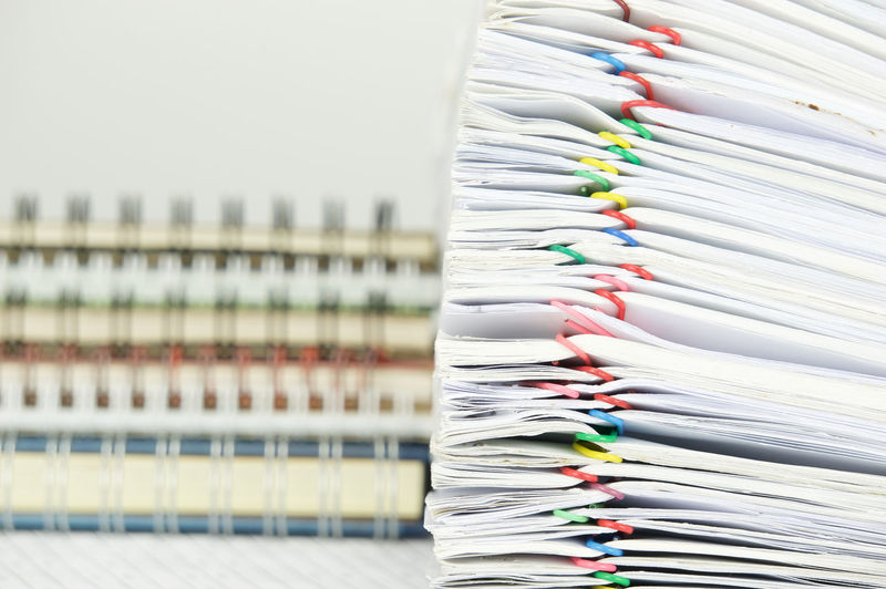 Stacked files and diaries against gray background