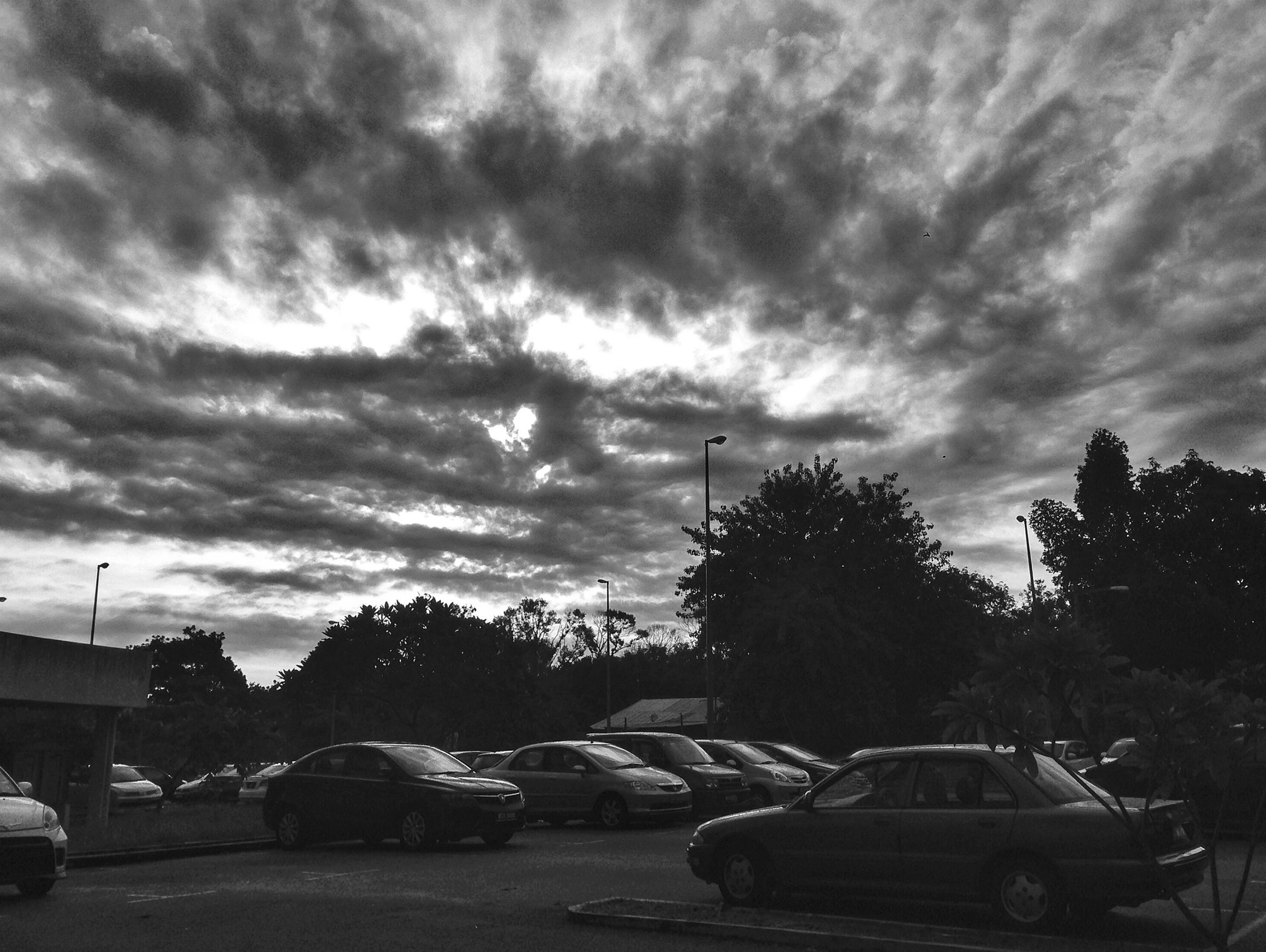 transportation, sky, mode of transport, land vehicle, car, cloud - sky, tree, cloudy, stationary, cloud, parking, parked, weather, overcast, outdoors, parking lot, road, nature, street, travel