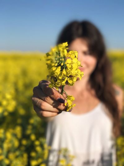 Young woman holding yellow flowers at oilseed rape field
