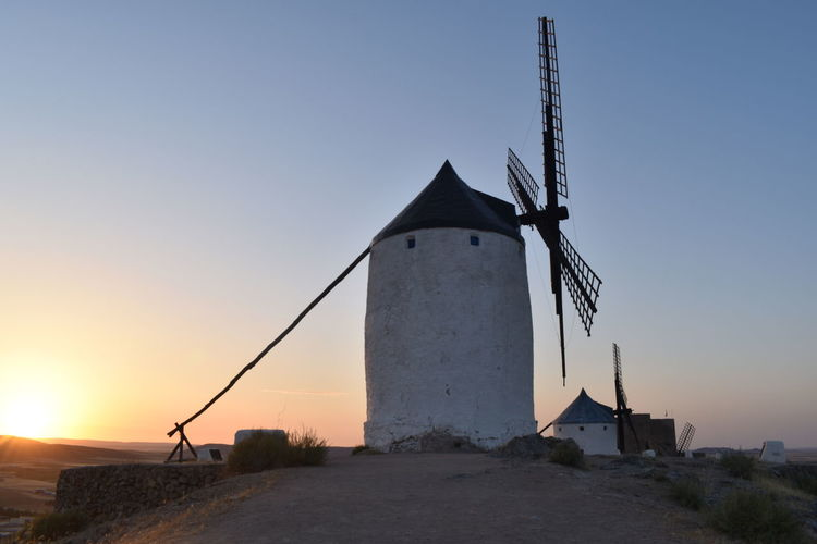 Traditional windmill against clear sky during sunset