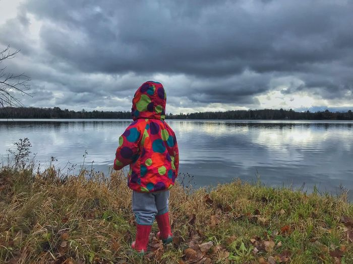 Rear view of boy standing by lake against sky