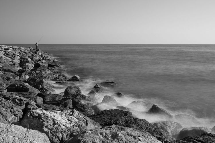 Man against the sea fishing. Man Mediterranean Sea Beach Blackandwhite Castelldefels Clear Sky Day Fishing Horizon Horizon Over Water Nature Outdoors Rocks Sea Sky Tranquility Water Wave