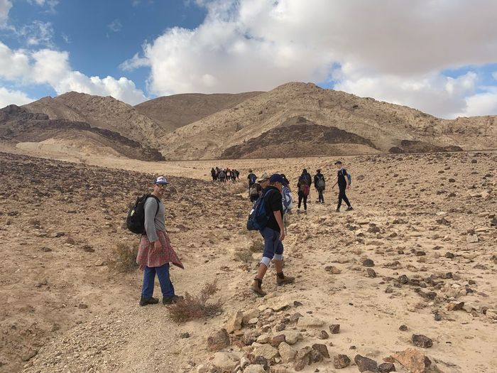 People walking on mountain road against sky