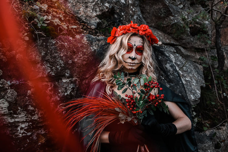 Closeup portrait of calavera catrina. young woman with sugar skull makeup and red flowers. dia