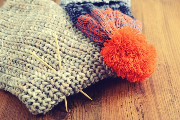 Close-up of knitting needles with hat and scarf on wooden table