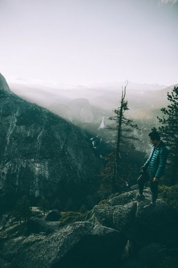 Side View Of Man With Camera Standing On Cliff During Foggy Weather