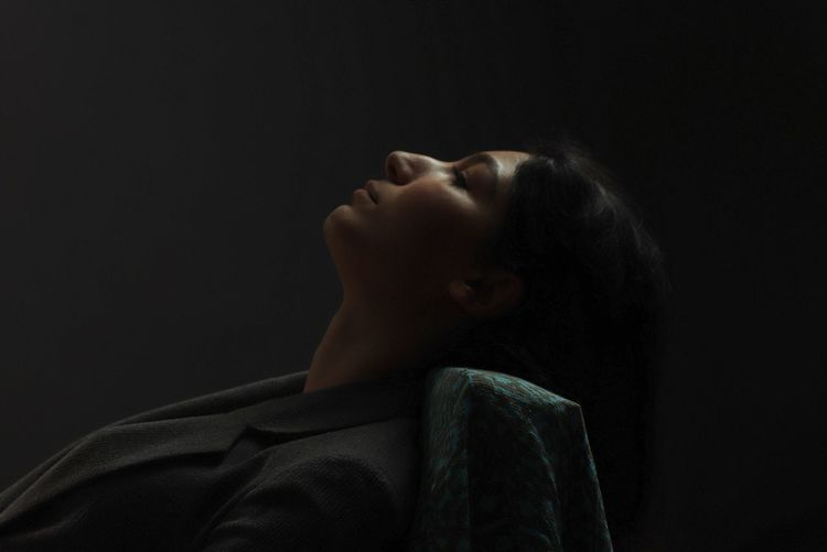 Side view of thoughtful woman sitting against black background