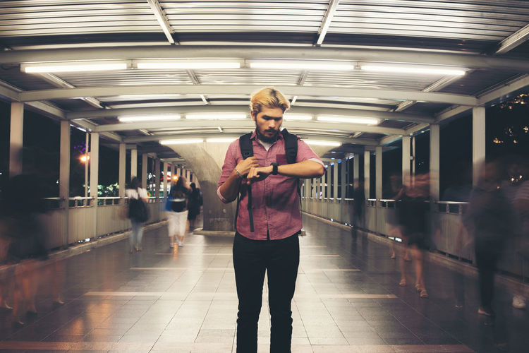 Young man looking at wristwatch while standing on footbridge at night