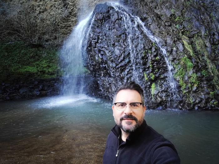 Portrait of man against waterfall